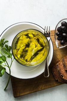 Сардины, маринованные в оливковом масле с ржаным хлебом, солью и перцем на столе