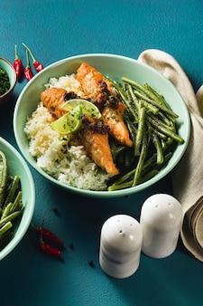 新鮮なサーモンを生姜とニンニクでココナッツミルクで炒め、バスマティライスとインゲンをテーブルのプレートで。家族全員のための健康的なレシピ。