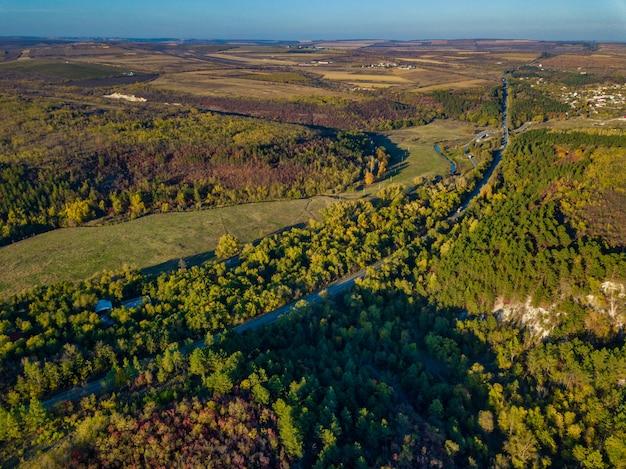 Вид с воздуха на красочный лес осенью с прорезать дорогу