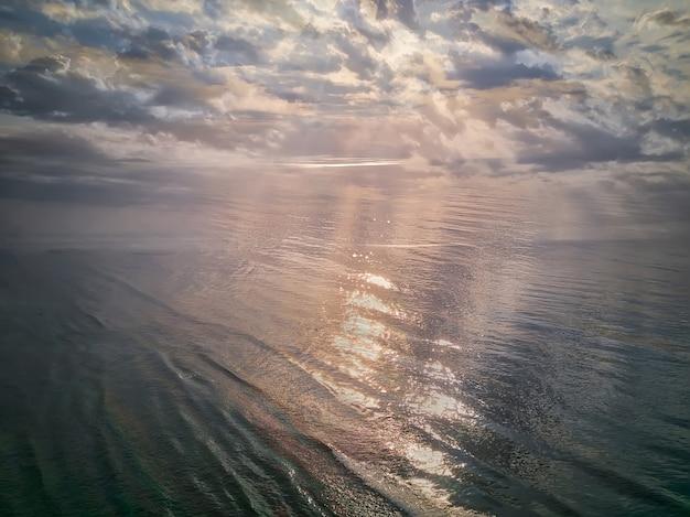日の出の空の空撮。海の上の朝の空の雲と空中の劇的な金の日の出。日の出の見事な空雲。航空写真。