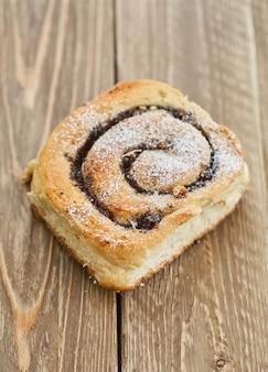 茶色の素朴な木製のテーブルにレーズンとおいしいパン。焼きたてのパン屋。朝ごはん。パン。上面図