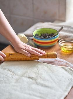 女性の手が生地を台所のテーブルに転がします。めん棒で女性の手