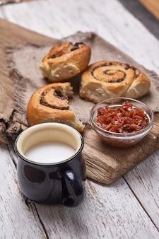 様々な自家製パイ生地パンシナモンミルクカップ、ジャム、バターを白い板の木製のテーブルで朝食として提供しています。フラットレイ、スペース