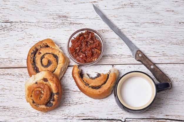 Разнообразие домашнее слоеного теста булочки с корицей подается с чашки молока, варенье, масло как завтрак на фоне белой доски деревянные.