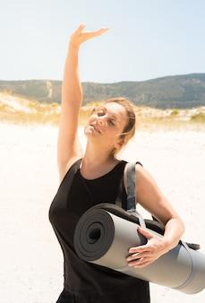 Женщина в спортивной одежде со свернутым ковриком под мышкой на пляже