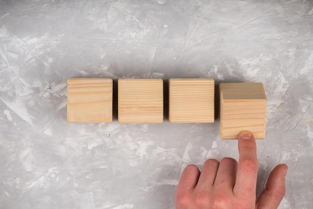 男の手が空の木製キューブ
