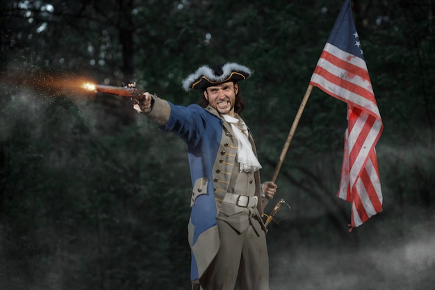 Человек, одетый как солдат американской революции, война соединенных штатов целится из пистолета с флагом