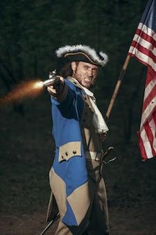Мужчина в костюме солдата войны за независимость сша целится из пистолета с флагом