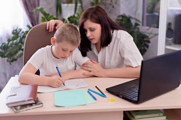 Мальчик школьник с мамой за столом и делает домашнее задание на ноутбуке