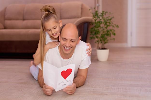 Счастливый молодой папа держит открытку от маленьких веселых дочерей в день отцов во время домашнего праздника