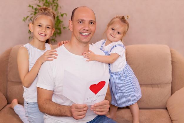 Папа держит открытку от маленьких веселых дочерей в день отцов во время домашнего праздника