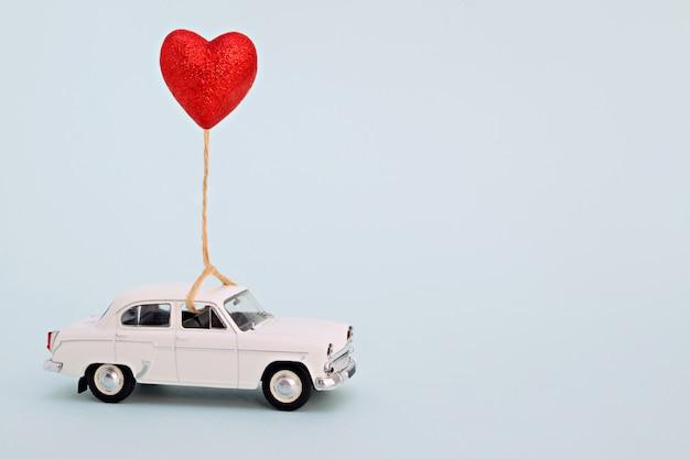 Белый ретро игрушечный автомобиль на день святого валентина с шариком в форме сердца.