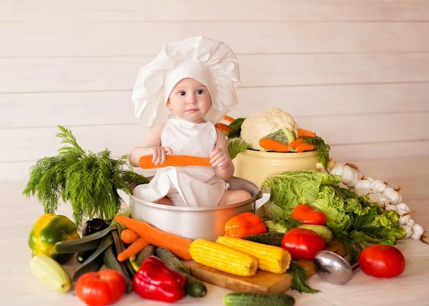 健康的な栄養エプロンと帽子で幸せな少女は、野菜のサラダを準備します。クック