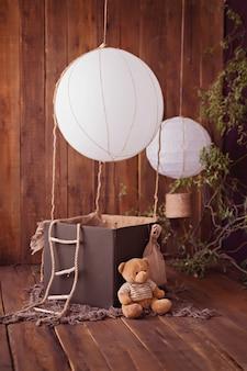 Плюшевый мишка с воздушным шаром на деревянном фоне