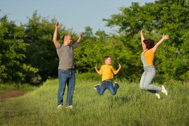 Семья: мама, папа, сын прыгают с поднятыми руками в зеленом поле летом