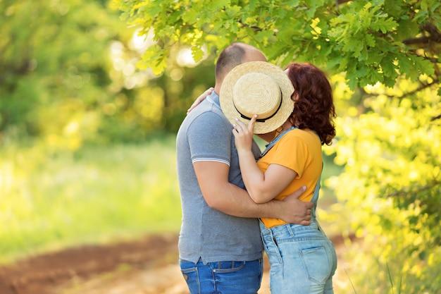 Счастливая семья, мужчина и женщина обнять, поцеловать друг друга на улице в летний вечер.