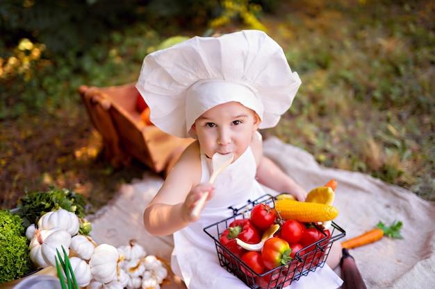 Концепция здорового питания. мальчик готовит овощной салат на природе в белом фартуке и шапке.
