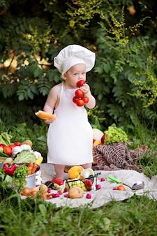 幸せな少年料理野菜のサラダを準備します。