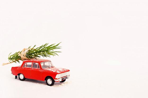 雪と冬の白い背景の上の赤いレトロなクリスマスツリー配信おもちゃの車