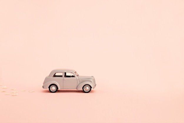 Серый ретро игрушечный автомобиль с доставкой цветов и подарков на розовом фоне