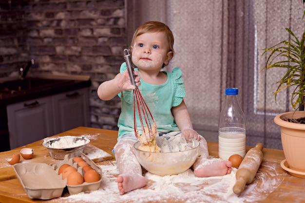 Счастливый ребенок девочка играет с мукой и готовит на кухне, замешивает тесто