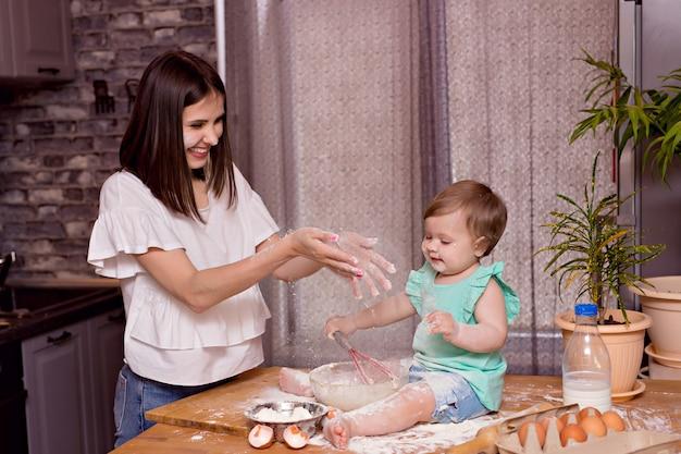 Счастливая семья, мама, дочка играют и готовят на кухне, замешивают тесто и пекут печенье