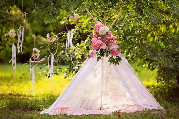 お祝いの装飾。リボン、花のテント。結婚式の装飾