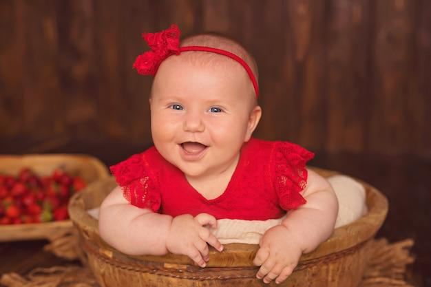 Счастливая улыбающаяся девочка в красном платье лежит на животе, ест клубнику и пьет молоко