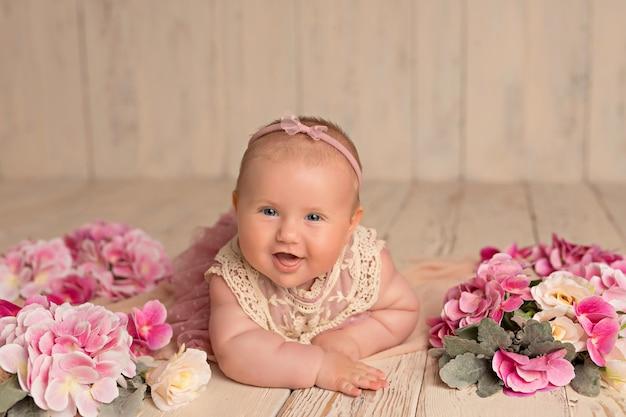 ピンクの花で幸せな笑顔の女の子は野生の花と彼女の胃にあります。