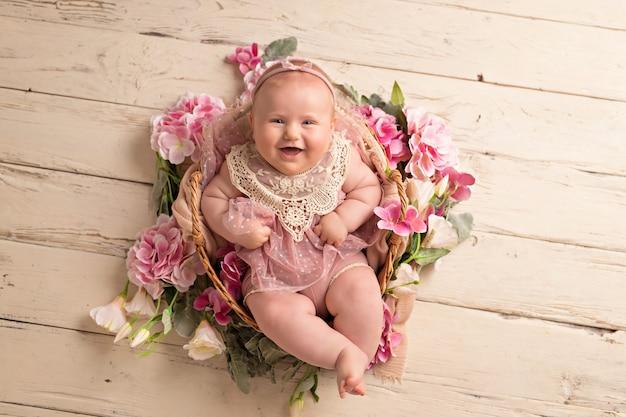 ピンクのドレスで幸せな笑みを浮かべて女の赤ちゃんはフラワーバスケットで彼女の背中にあります。