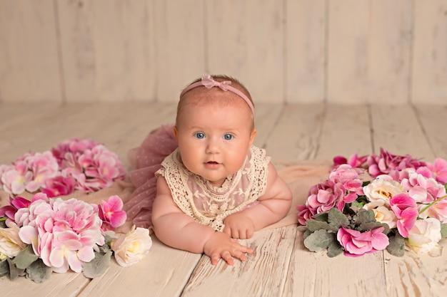 ピンクのドレスで幸せな笑顔の女の子は繊細な花で彼女の胃にあります。