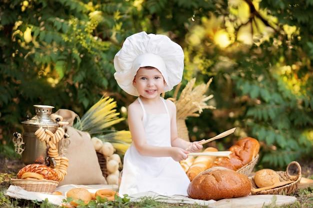 Малыш пекарь на пикнике ест хлеб и бублики в белом фартуке и шапке на природе в солнечный летний день