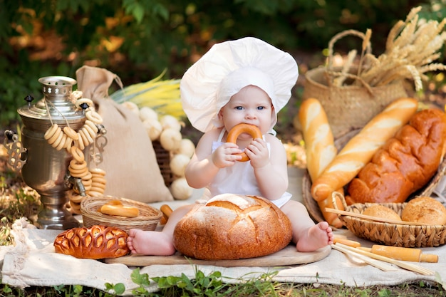 Девушка готовит на природе в солнечный летний день. малыш пекарь ест хлеб и бублики в белом фартуке