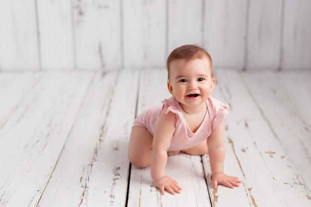 Девочка в розовом боди ползет по полу