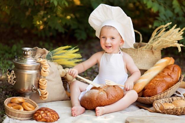 少年は自然の中で野菜のサラダを調理します。庭師は野菜の収穫を収集します。商品のお届け
