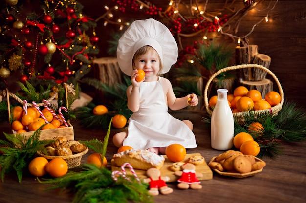 赤ちゃん料理人がジンジャーブレッドクッキーを準備します。メリークリスマス、みかん、クリスマスツリー