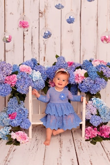 Счастливая девушка в голубом платье сидит на кровати с голубыми и розовыми цветами гортензии