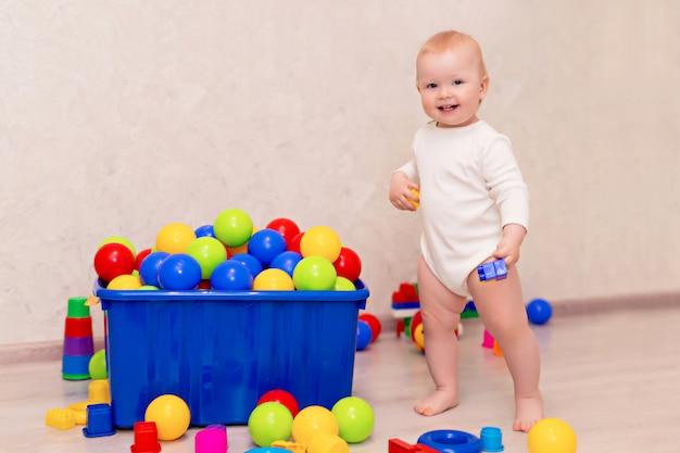 Малыш в белой одежде сидит и играет с шариками