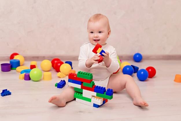 Малыш в белой одежде сидит и играет с разноцветными шариками