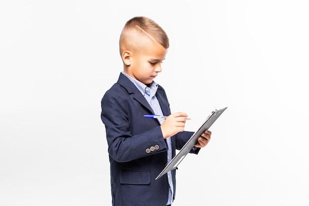 Школьник в костюме показывает чистый лист буфера обмена, изолированные на белой стене