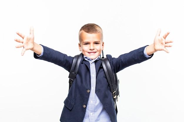 白い壁に変なポーズを作る小さな学校の男の子