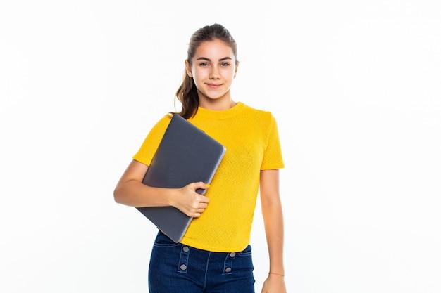 Улыбается милая девушка с помощью ноутбука на белой стене