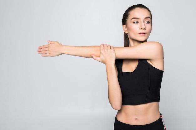 Портрет улыбающегося фитнес женщины протягивая руки над белой стеной