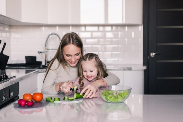 母と子の娘が野菜サラダを準備しています