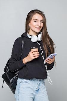 携帯電話と白い壁で隔離のイヤホンで音楽を聴いて幸せな若い女の肖像