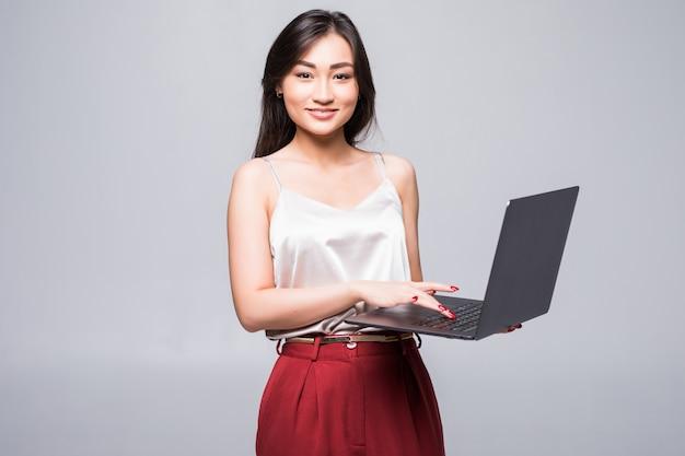 Портрет счастливой азиатской женщины работая на портативном компьютере изолированном над белой стеной