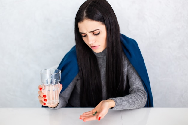 Молодая красивая женщина у себя дома на белом столе чувство недомогания и кашель как симптом простуды или бронхита. концепция здравоохранения.