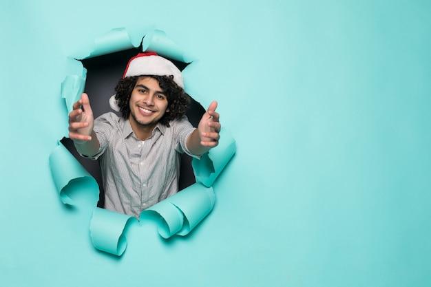 Молодой кудрявый красавец носить в новогодней шапке с пальцами вверх из отверстия на зеленой бумаге
