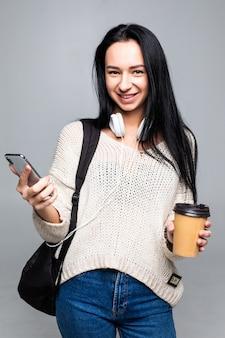 Молодые женщины, держа смартфон и чашку кофе, изолированные на серую стену