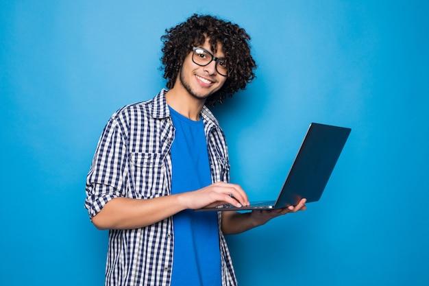 水色の壁に分離されたラップトップで若い巻き毛のハンサムな男